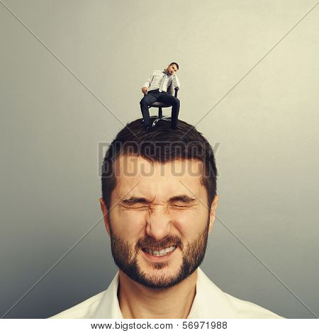 bored small man sitting on the head of another man