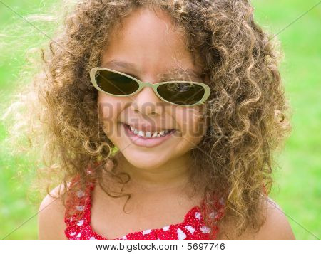 Young Girl With Bright Smile Wearing Sunglasses
