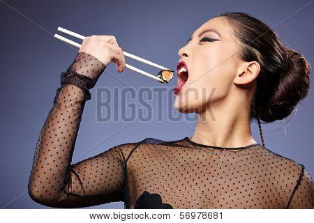 Sushi woman holding sushi with chopsticks