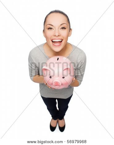 banking and investment concept - laughing woman with piggy bank