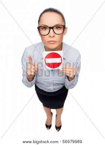 business, protest and office concept - concerned businesswoman in eyeglasses showing stop sign with finger up