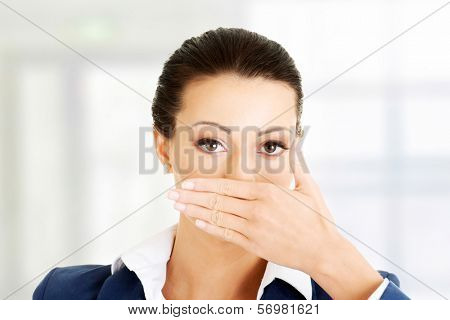 Portrait of young business woman covering with hand her mouth