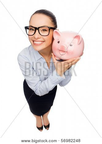 business, banking, investment and office concept - smiling businesswoman in eyeglasses with piggy bank