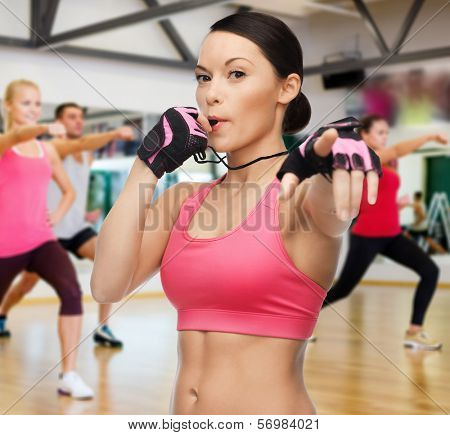 fitness, sport, training, gym and lifestyle concept - beautiful sporty woman with whistle in gym
