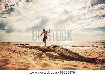 Boy Balancing on a washed up tree trunk on the beach