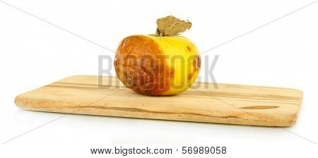 Rotten apple on wooden board isolated on white