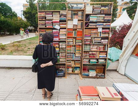 SARAJEVO, BOSNIA AND HERZEGOVINA - AUGUST 11, 2012: Woman perusing bookshelves on street market, common occurrence in the cultural city of Sarajevo.
