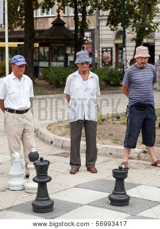 SARAJEVO, BOSNIA AND HERZEGOVINA - AUGUST 11, 2012: Men play chess on street with large chess pieces in the centre of Sarajevo.