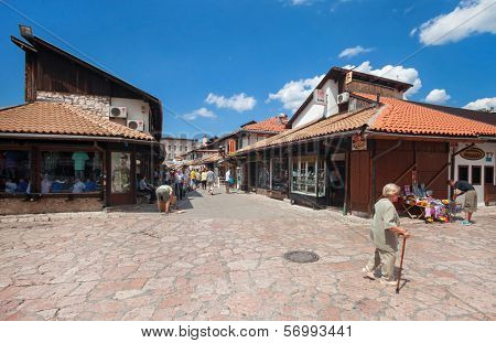 SARAJEVO, BOSNIA AND HERZEGOVINA - AUGUST 11, 2012: Old woman in market area of Bascarsija,  old market-place, historical and cultural centre of Sarajevo city.