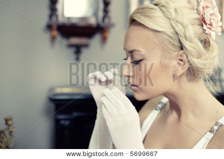 Portrait Of Beautiful Young Woman Smelling A Bottle Of Perfume