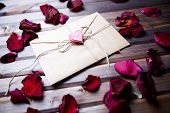 Image of letter of love with small pink heart surrounded by rose petals