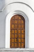 foto of entryway  - Modern Wooden door of a white stone wall entrance to the Christian church - JPG
