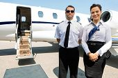 image of flight attendant  - Portrait of confident stewardess and pilot standing against private jet - JPG