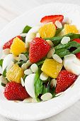 picture of quail egg  - Spinach strawberry orange quail eggs salad with almonds slices and balsamic vinegar on white plate