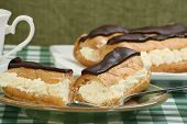 stock photo of eclairs  - delicious cream filled chocolate eclairs on a green table cloth - JPG