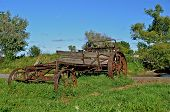 picture of spreader  - A very old dilapidated manure spreader is parked in a field as it continues to deteriorate - JPG