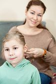 foto of raid  - Mother raiding the hair of her child sitting in domestic room - JPG