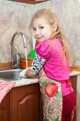 foto of wash-basin  - Caucasian pretty girl in the kitchen washing dishes - JPG