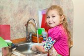 image of wash-basin  - Small girl in the kitchen washing dishes copyspace - JPG