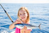foto of troll  - Blond kid girl fishing tuna little tunny happy with trolling catch on boat deck - JPG