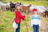 image of shepherdess  - Kid girl shepherdess sisters happy with flock of sheep and wooden stick in Spain - JPG