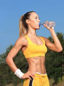 Athlete woman drinking water from a bottle