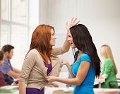 bullying, school, education,friendship and people concept - two teenagers having a fight and getting