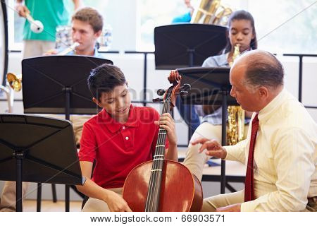 Boy Learning To Play Cello In High School Orchestra