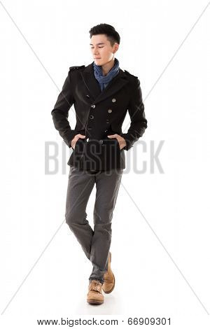Attractive young Asian man in winter coat, full length portrait isolated on white background.