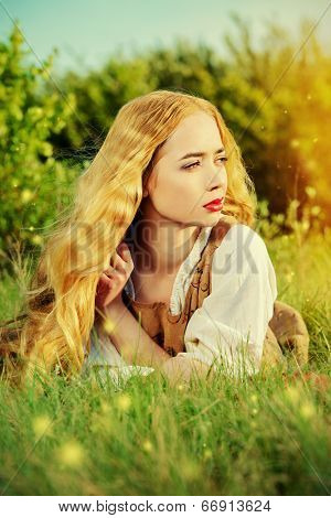 Beautiful young woman with magnificent blonde hair posing outdoor. Countryside, meadow.