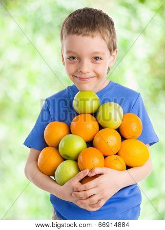 Happiness boy with apples and oranges outdoors