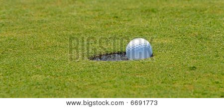 Golf putt into hole