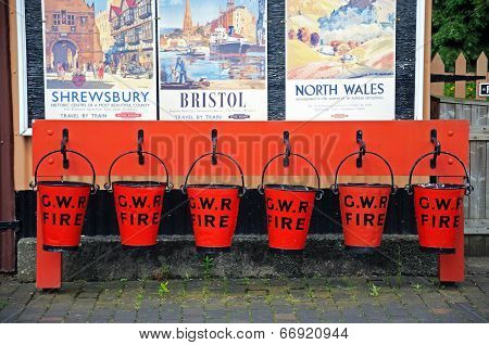 Row of red fire buckets.