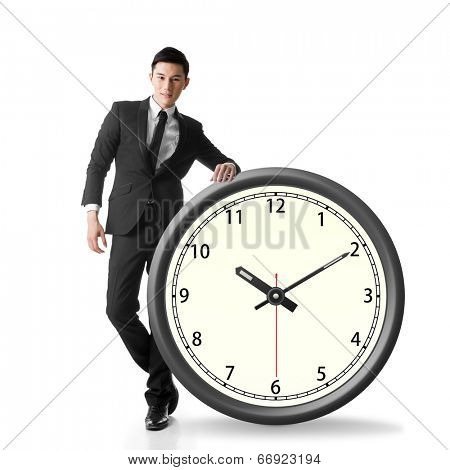 Asian businessman standing with a clock, concept of time manage or plan.