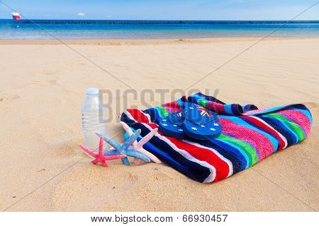beach towel and bottle of water on sandy beach