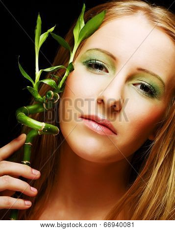 woman with bamboo on black background