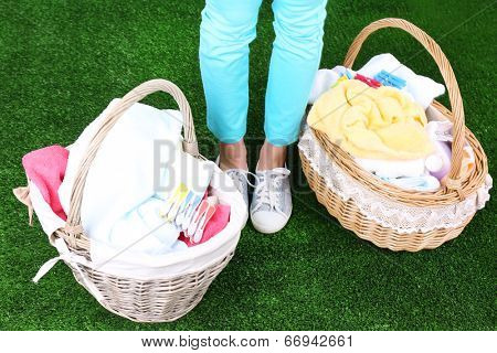 Woman holding laundry baskets with clean clothes, towels and pins, on green grass background