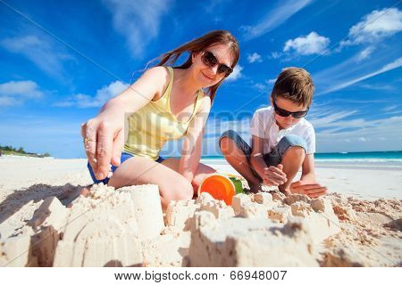 Young mother and her son at tropical beach making sandcastle