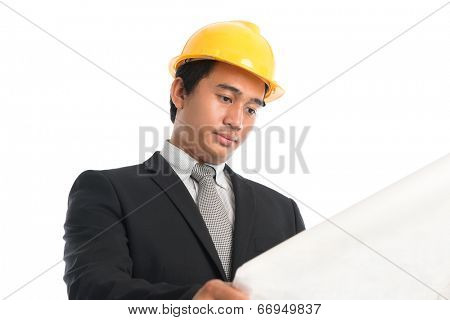 Close-up of an Asian young man wearing a hardhat looking at blueprint paper, standing isolated on white background.