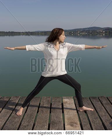 Yoga Woman In Warrior II Pose In Nature