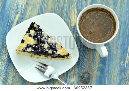 piece of delicious homemade fruity sponge cake with blueberries and cup of coffee