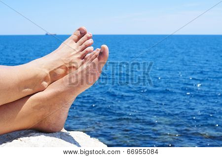 bare feet of a man who is relaxing near the ocean in the summer