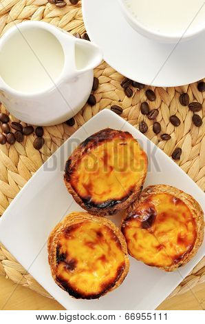 a jar and a cup with milk, and some pasteis de nata typical Portuguese egg tart pastries, on a set table