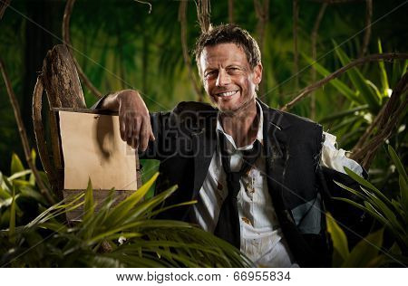 Survivor Businessman Leaning To A Sign In The Jungle