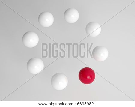 One different red ball in a circle of white balls at an oblique angle with perspective conceptual of diversity, individuality and leadership
