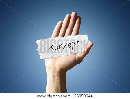 Man holding up a scrap of white paper with the german word - Konzept - in script, close up of his hand on a blue background with a side vignette in a conceptual image