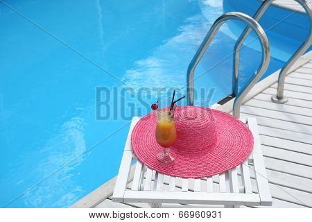 Cocktail With Cherry On A Beach Table With A Straw Hat Near