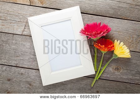 Three colorful gerbera flowers and photo frame on wooden table