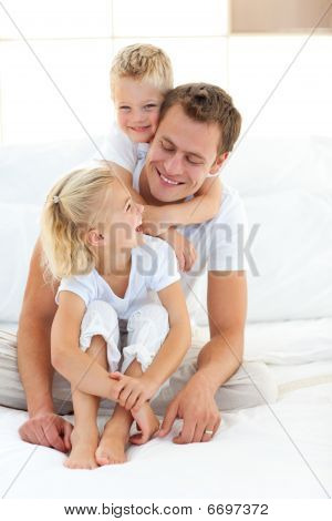Attentive Attractive Father Playing With His Children On A Bed