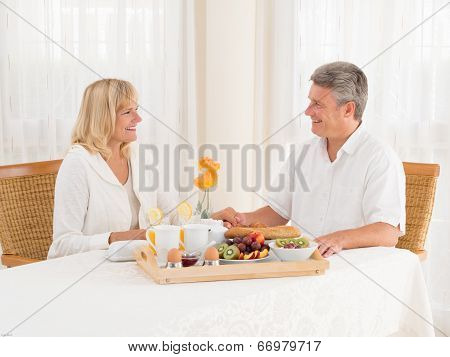 Happily Mature Senior Married Couple Enjoy A Healthy Breakfast Holding Hands